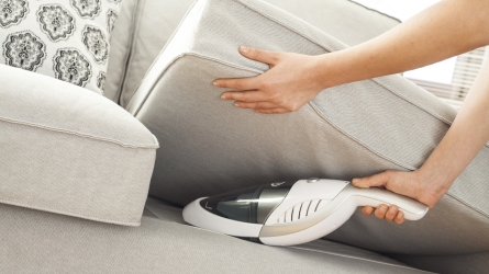 handheld vacuum being used on couch