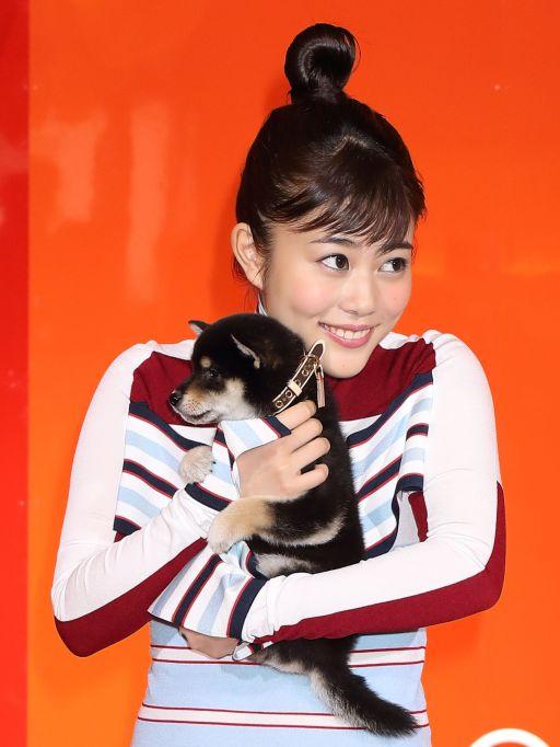 Mitsuki Takahata holding a puppy