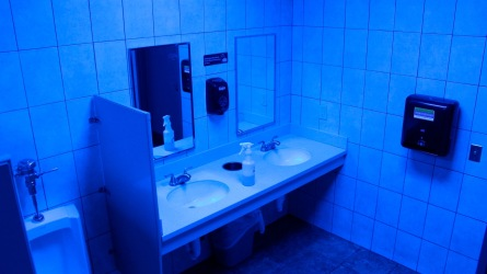 A public bathroom bathed in blue