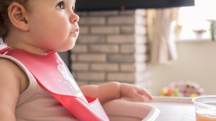 toddler wearing plastic bib