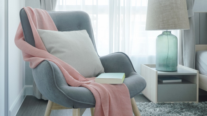 armchair with blanket and throw pillow
