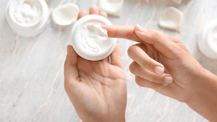 Woman holding anti-aging moisturizer cream