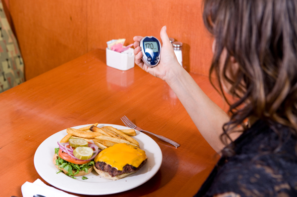 Woman checking blood sugar before meal