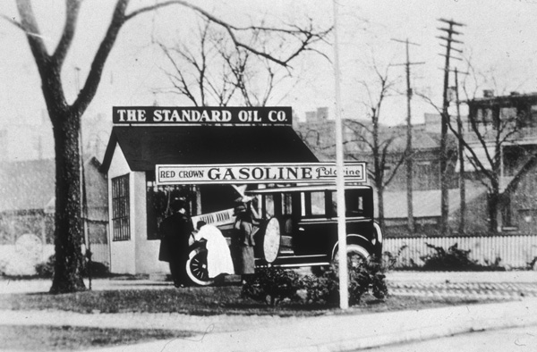 Three people look under the hood of an automobile in front of a Standard Oil gas station. (Photo credit: Hulton Archive/Getty Images)