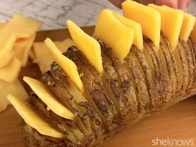pushing cheese slices in between the slats of a hasselback potato