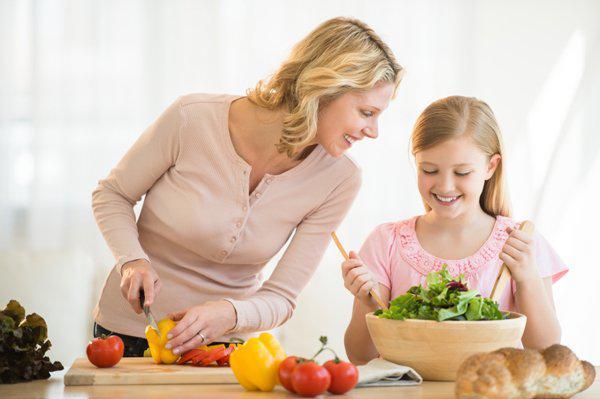 mother and daughter preparing salad