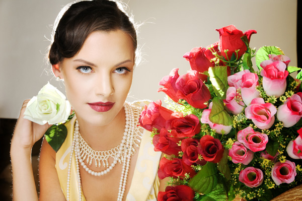 Woman with a pearl necklace holding a rose.