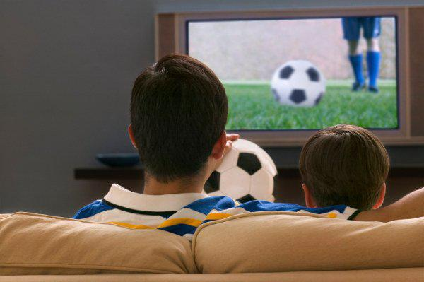 father and son watching soccer on tv