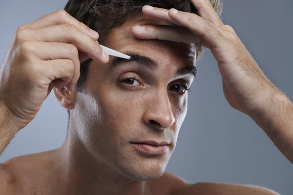 Man tweezing eyebrows