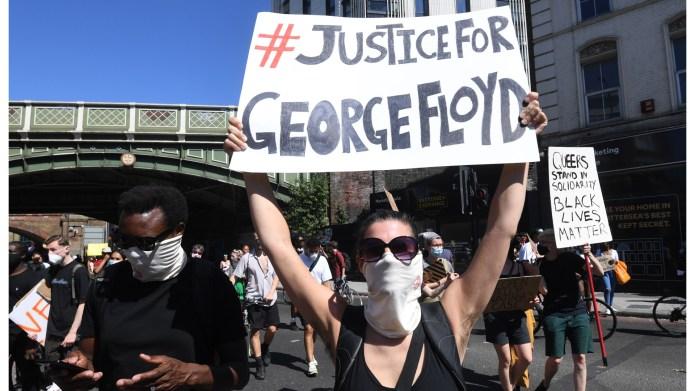 Protester holding sign: #JusticeForGeorgeFloyd